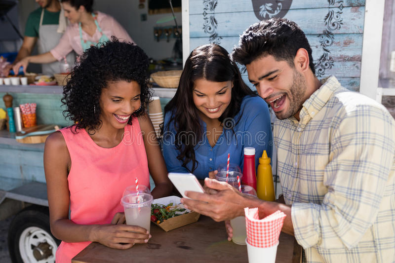 Przyjaciele używa telefon komórkowego przy jedzenie ciężarówki samochodem dostawczym zdjęcia royalty free