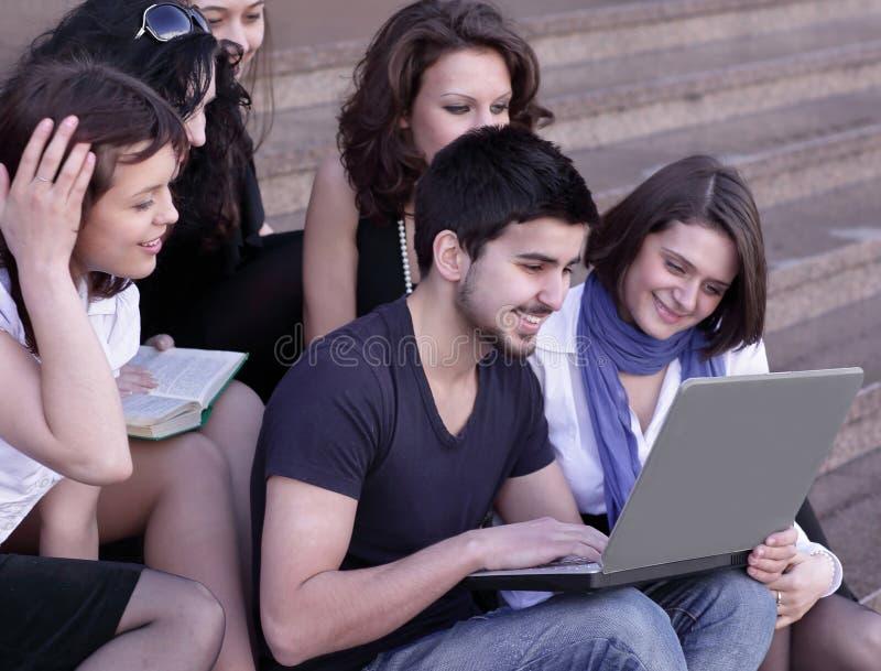 Przyjaciele ucznie patrzeje laptopu ekran zdjęcie stock