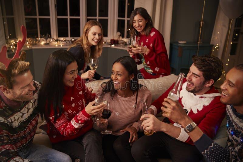 Przyjaciele W Świątecznych bluzach Świętują Przy przyjęciem gwiazdkowym obraz royalty free