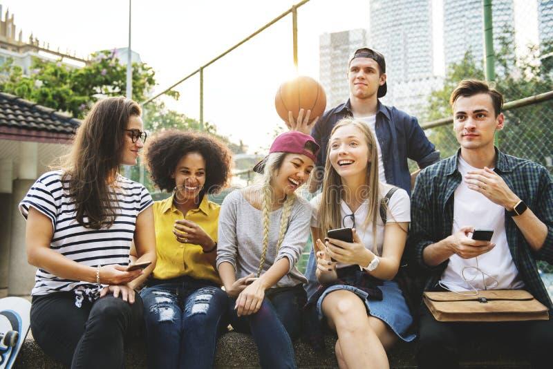 Przyjaciele w parkowych patrzeje używa smartphones millennial i tobie obraz royalty free