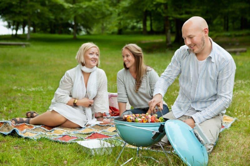 Przyjaciele w Parkowym Jeść BBQ pinkinie zdjęcia royalty free