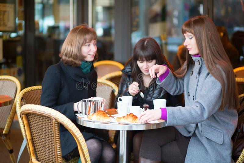 Przyjaciele w Paryjskiej ulicznej kawiarni zdjęcia stock