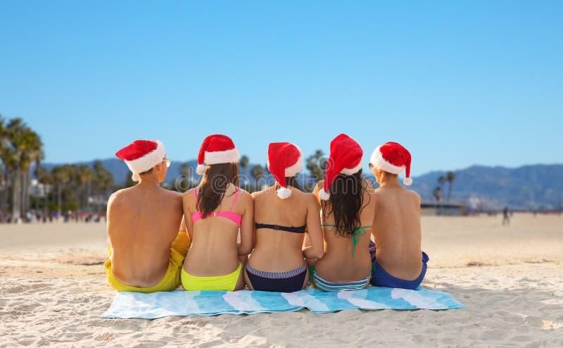 Przyjaciele w Santa kapeluszach na Venice wyrzucać na brzeg na bożych narodzeniach obraz royalty free
