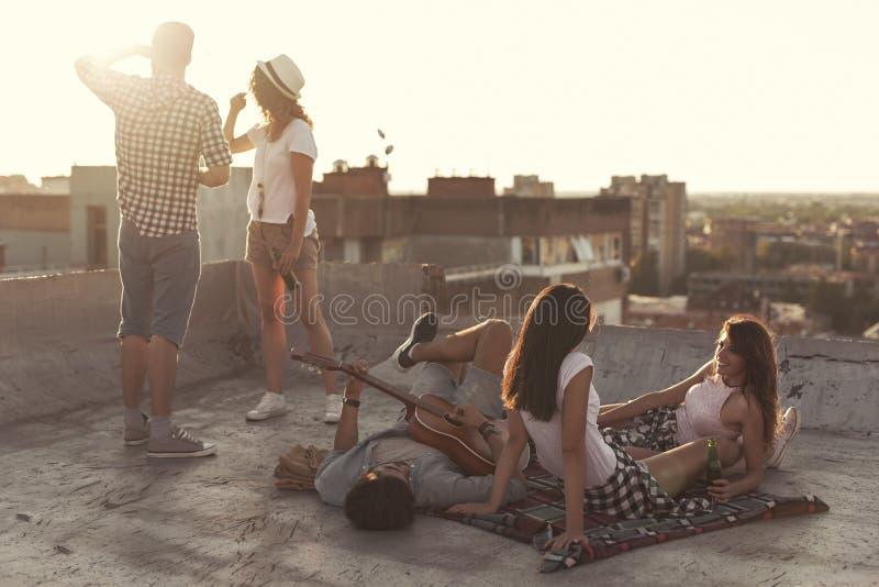Przyjaciele wiszący na budynku dachu out obrazy stock