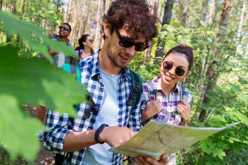 Przyjaciele wycieczkuje w lesie z mapą i plecaki fotografia stock