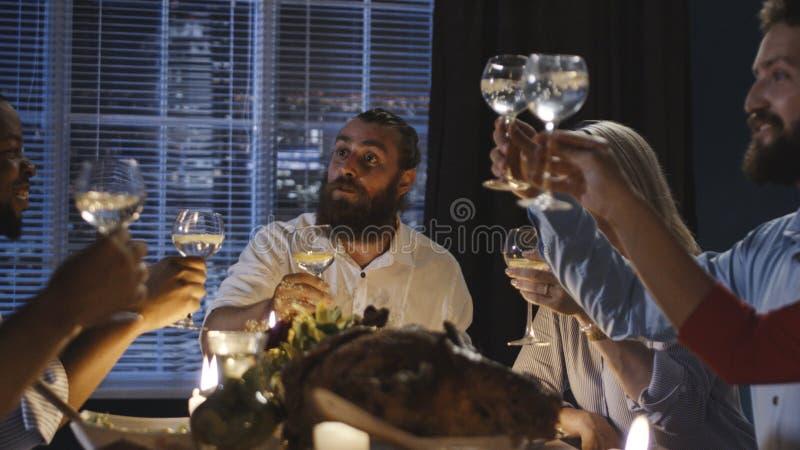 Przyjaciele wznosi toast przy stołem na dziękczynienie dniu zdjęcie royalty free