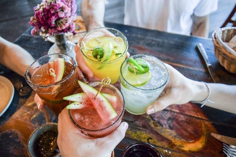 Przyjaciele wznosi toast z tropikalnymi napojami fotografia stock