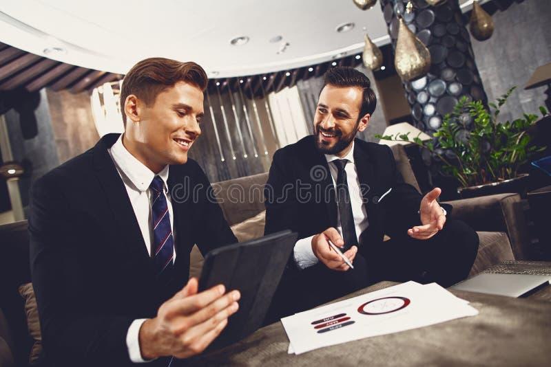 Przyjazni partnerzy biznesowi uÅ›miechajÄ… siÄ™ podczas omawiania projektu zdjęcia stock