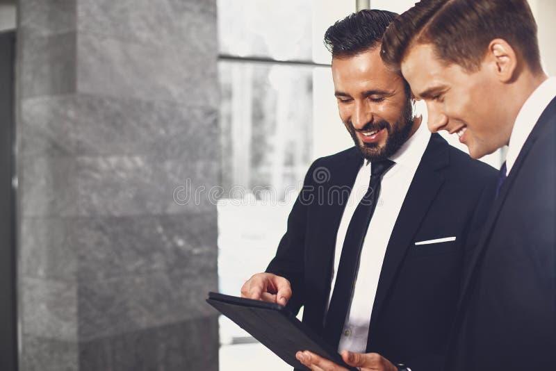 Przyjazni partnerzy biznesowi wskazujÄ…cy tablet i uÅ›miechajÄ…cy siÄ™ fotografia stock