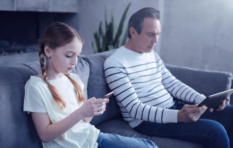 Przyjemna ładna dziewczyna patrzeje jej smartphone ekran fotografia royalty free