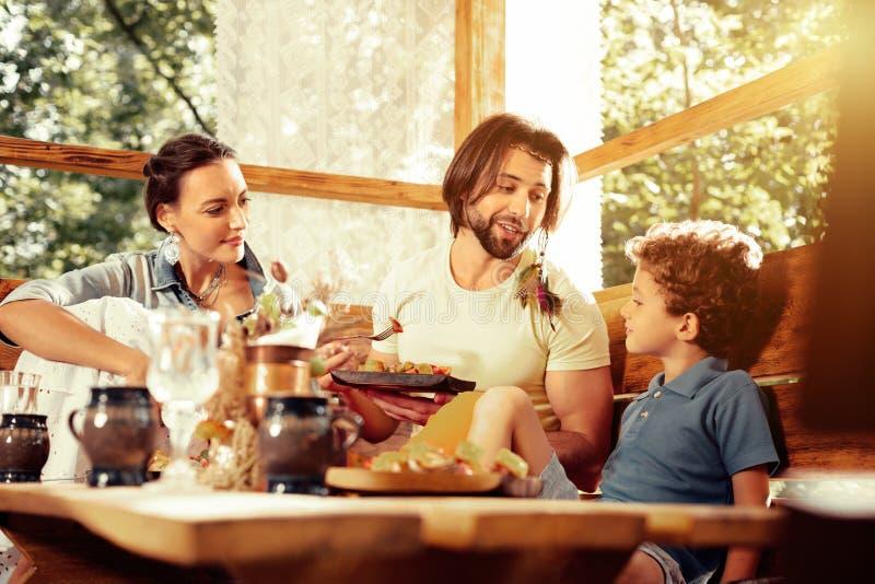 Przyjemna śliczna chłopiec ma posiłek z jego rodziną obrazy royalty free