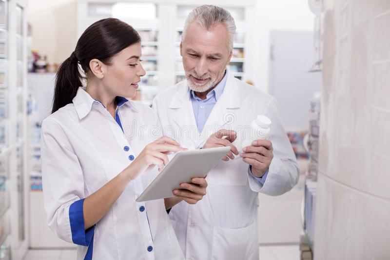 Przyjemna żeńska farmaceuta konsultuje z kolegą obrazy stock