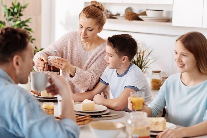 Przyjemna życzliwa rodzina pije herbaty wpólnie zdjęcie royalty free