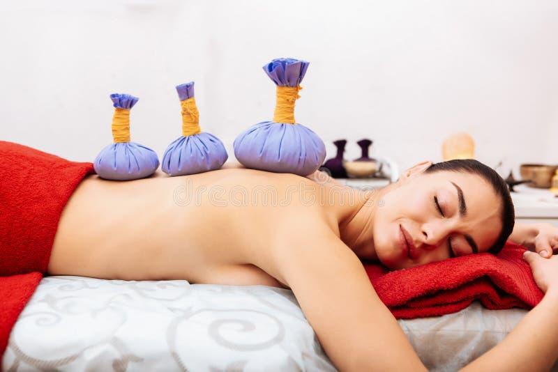Przyjemna ciemnowłosa kobieta odpoczywa na masażu łóżku z doskonałą skórą zdjęcia stock