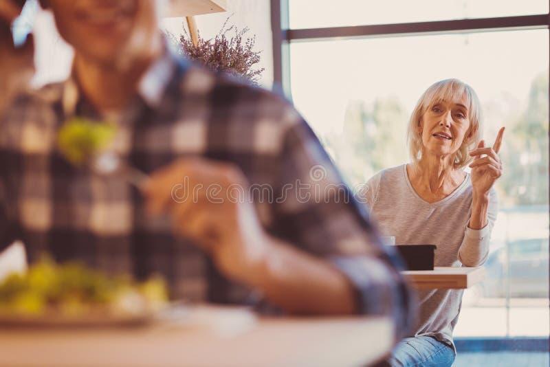 Przyjemna kobieta dzwoni w górę kelnera w kawiarni fotografia stock