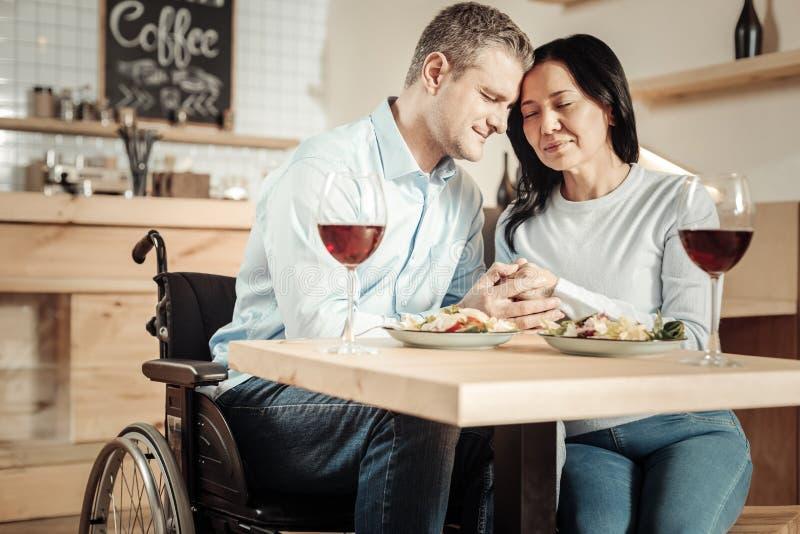 Przyjemna kobieta i jej niepełnosprawny mąż ma lunch zdjęcia stock