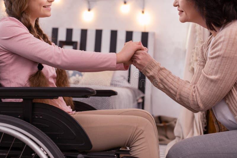 Przyjemna kobieta i niepełnosprawna dziewczyna łączy ręki zdjęcie stock