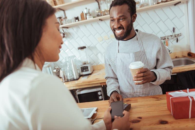 Przyjemna kobieta używa NFC technologię płacić w kawiarni fotografia royalty free