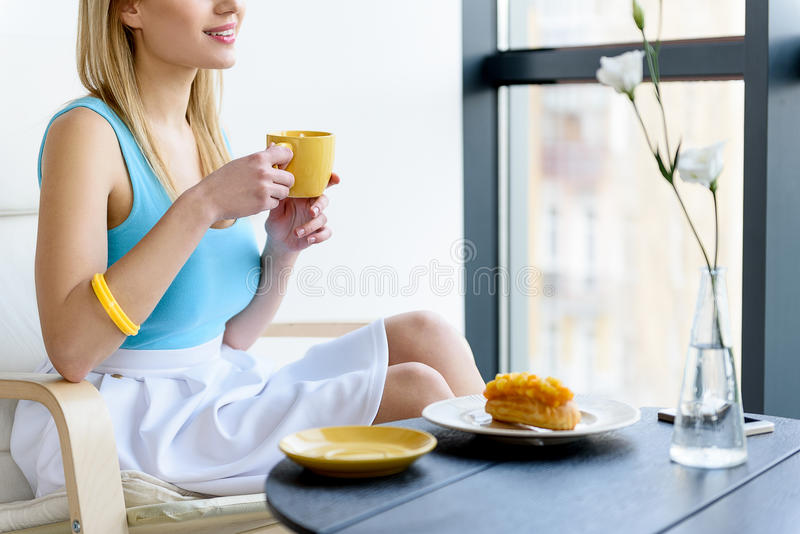 Przyjemna młoda kobieta cieszy się jej napój fotografia stock