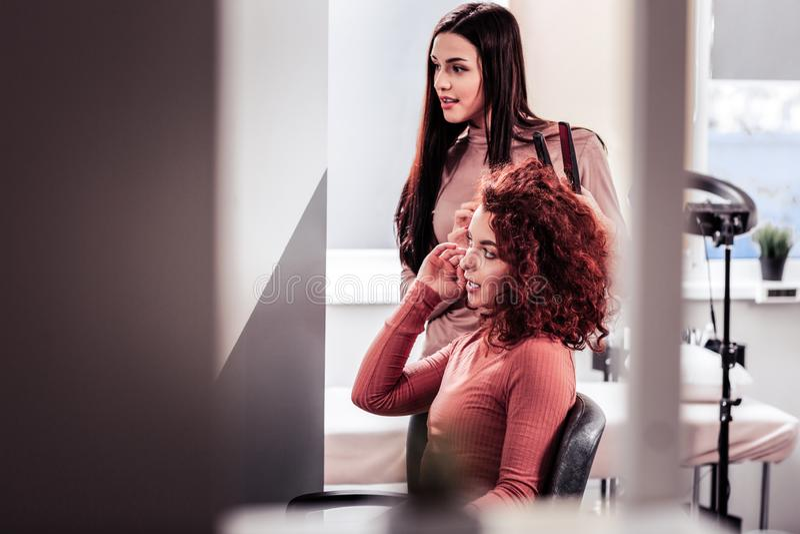 Przyjemna młoda kobieta mówi jej włosiany stylista obrazy stock
