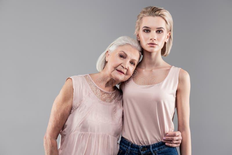 Przyjemna starsza dama ściska jej uroczej córki z jeden ręką obrazy stock