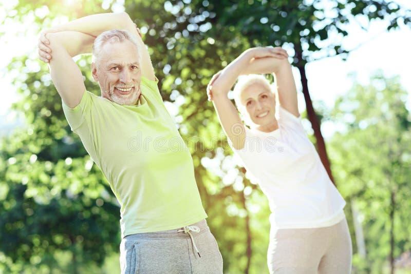 Przyjemna starzejąca się para patrzeje szczęśliwy podczas gdy trenujący fotografia stock