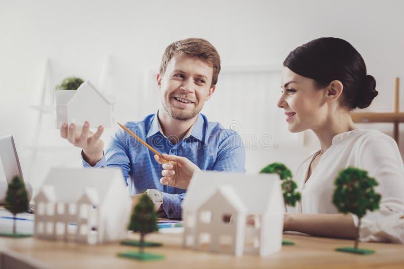 Przyjemna szczęśliwa kobieta wskazuje przy domowym modelem zdjęcia stock