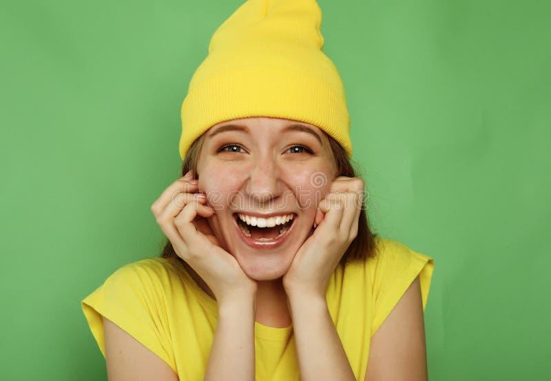 Przyjemnie zdziwione uśmiechnięte młodej dziewczyny mienia ręki na policzkach z szeroko otwartym usta w zdumieniu obraz stock