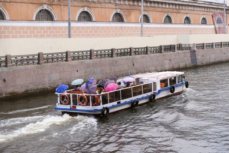 Przyjemności łódź z turystami z parasolami w chmurnej pogodzie na Moika rzece w St Petersburg zdjęcia royalty free