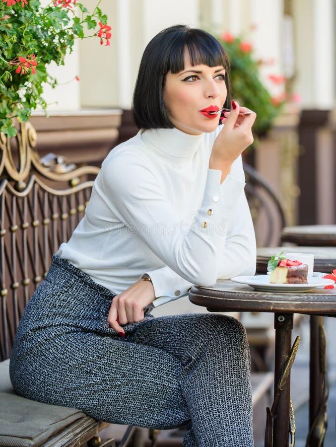 Przyjemny czas i relaks Wy?mienicie smakosza tort Kobiety atrakcyjna brunetka je smakosz kawiarni tarasu tortowego t?o fotografia royalty free