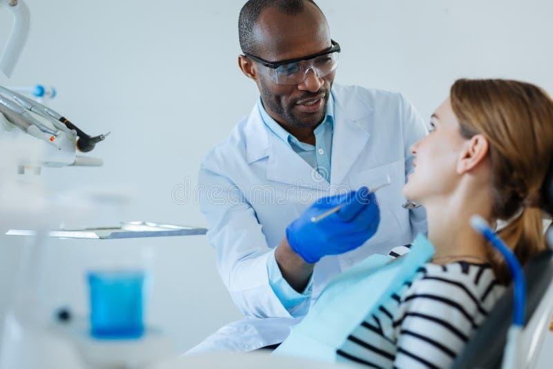 Przyjemny dentysta wyjaśnia traktowanie protokół pacjent zdjęcia stock