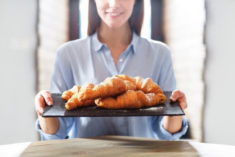 Przyjemny kobiety mienia talerz z croissants zdjęcie stock