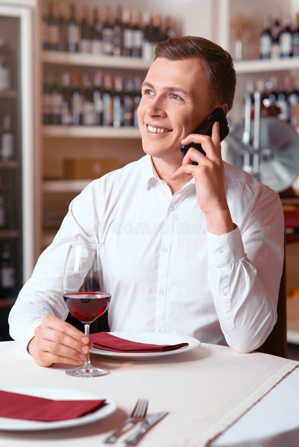 Przyjemny mężczyzna obsiadanie przy stołem w restauraci zdjęcie royalty free