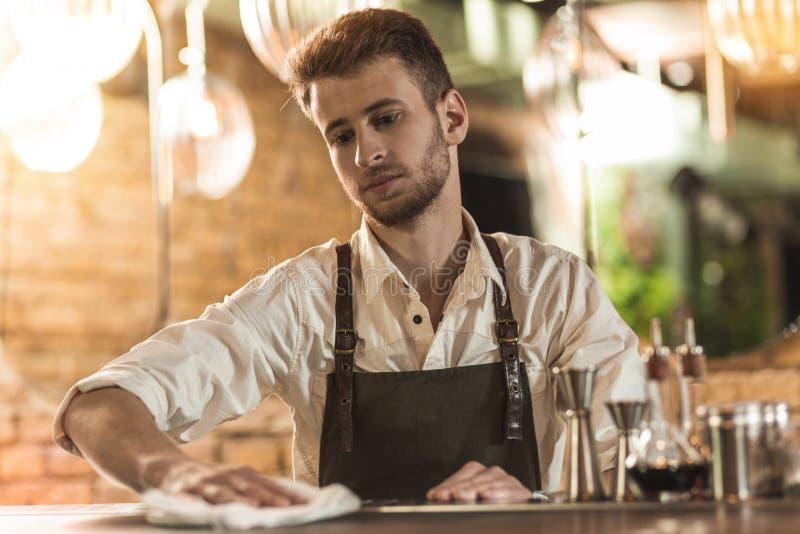 Przyjemny młody barmanu cleaning bar odpierający z płótnem zdjęcie stock
