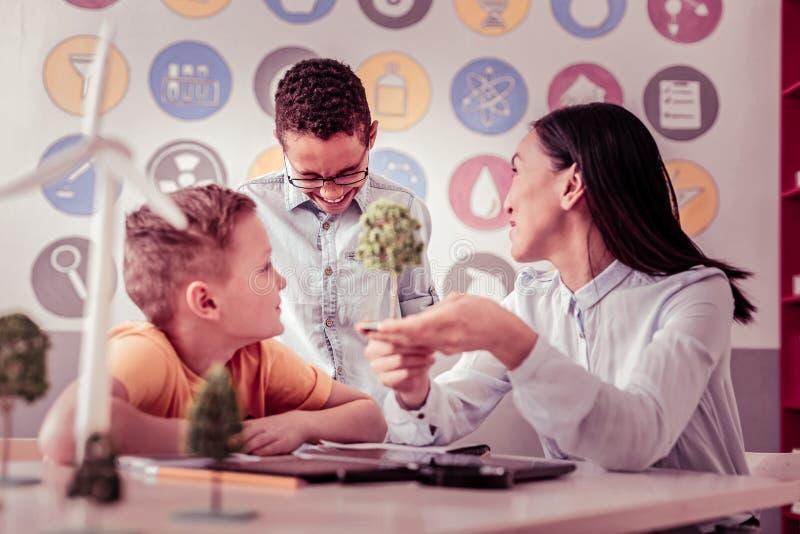 Przyjemny nauczyciel demonstruje modela drzewo jej ucznie obrazy stock
