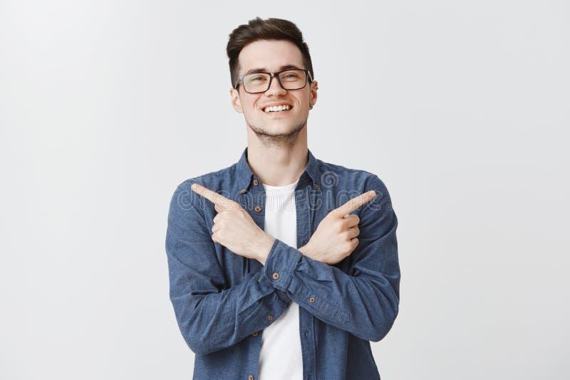Przyjemny przyglądający powabny uśmiechnięty facet w szkłach i błękitnym koszulowym skrzyżowaniu ręk na ciele, wskazywać z ukosa  zdjęcie stock