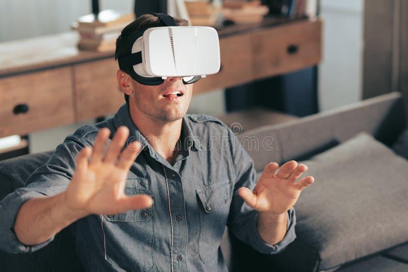 Przyjemny przystojny mężczyzna jest ubranym rzeczywistość wirtualna szkła obrazy stock