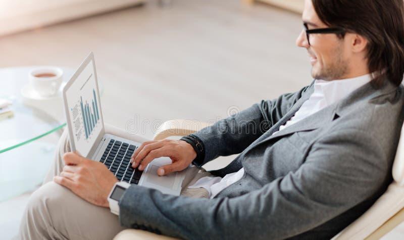 Przyjemny uśmiechnięty biznesmen używa laptop obrazy stock