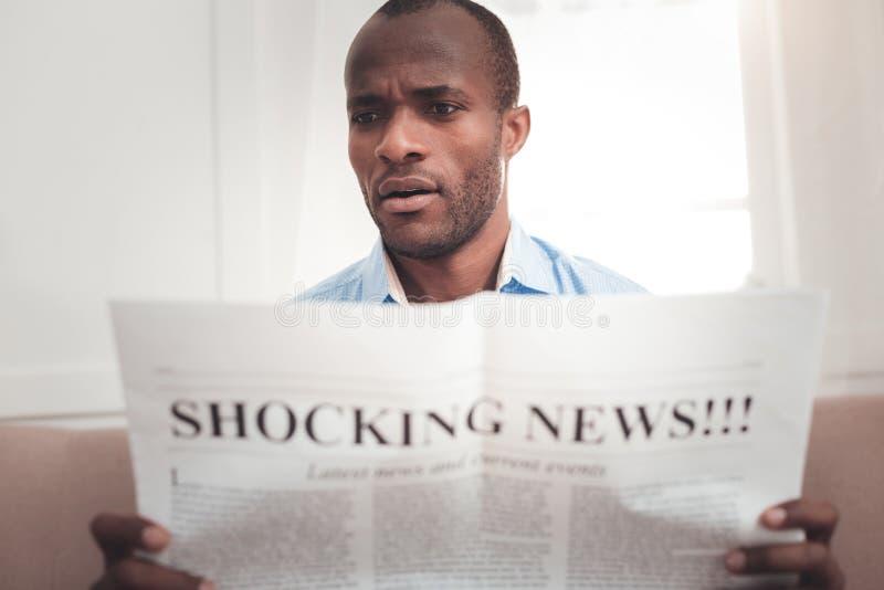 Przyjemny zdziwiony mężczyzna czyta gazetę zdjęcie royalty free