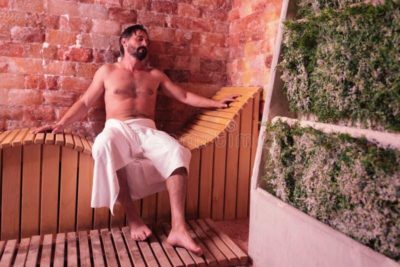 Przyjemny zrelaksowany mężczyzna cieszy się jego czas w sauna obraz royalty free