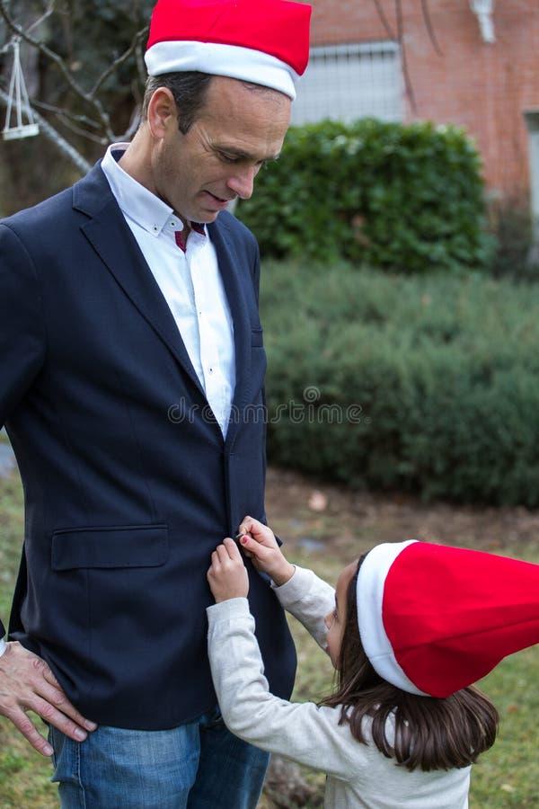 Przymocowywać jej ojca ` s kurtki wirh Santa kapelusz zdjęcie royalty free