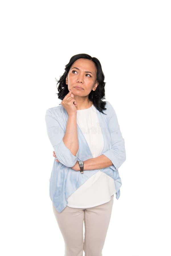 Przypadkowa azjatykcia kobieta w rozważnej pozie odizolowywającej na bielu obraz stock
