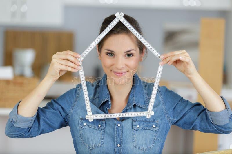 Przypadkowa dama robi domowemu kształtowi od pomiarowej władcy fotografia royalty free