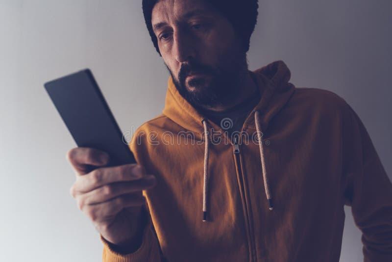 Przypadkowa dorosła samiec patrzeje telefon komórkowego z nakrętką zdjęcie stock
