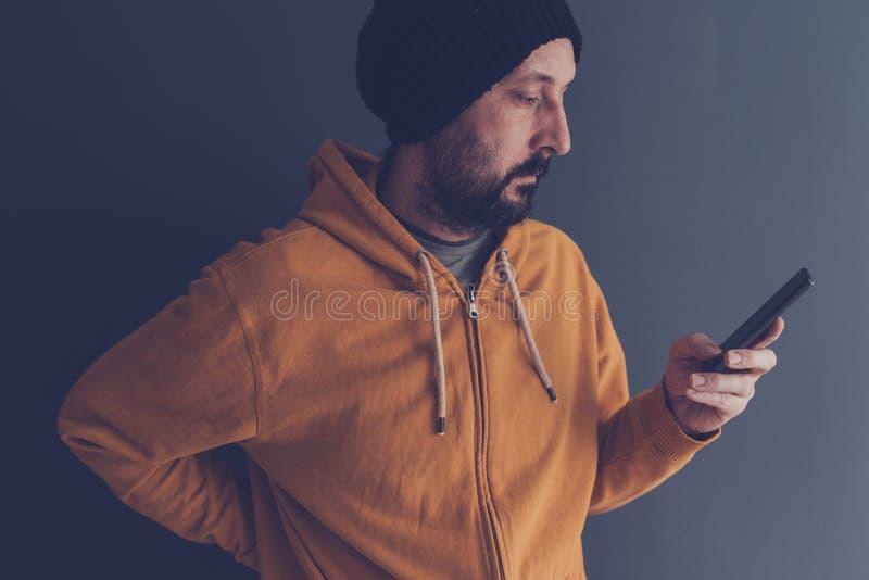 Przypadkowa dorosła samiec patrzeje telefon komórkowego z nakrętką zdjęcie royalty free
