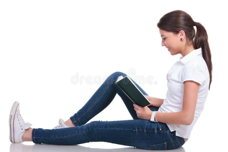 Przypadkowa kobieta kłaść na podłoga & czyta fotografia stock