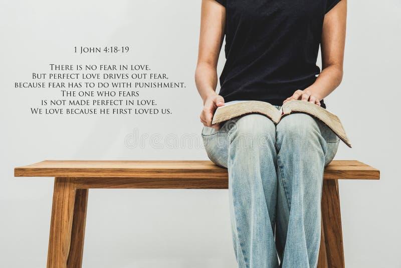 Przypadkowa młoda kobieta trzyma otwarty biblii 1 John 4:18 - 19 na ona podołek obraz royalty free