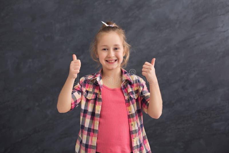 Przypadkowa mała dziewczynka pokazuje aprobaty przy szarym tłem zdjęcie royalty free