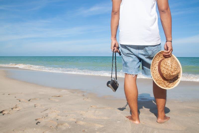 Przypadkowego stylu mężczyzna z kamery i kapeluszu odprowadzeniem na plaży, Szczęśliwej zdjęcia royalty free