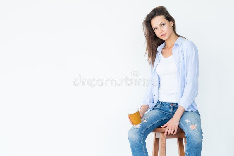 Przypadkowej kobiety stolec chwyta filiżanki siedzący biel obrazy royalty free